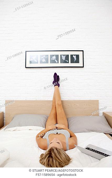 Young woman relaxing on her bed on her laptop