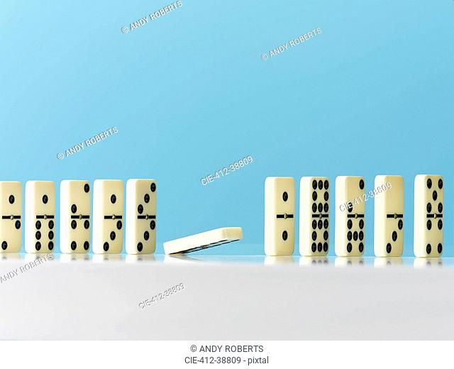 Domino falling in a row on blue background