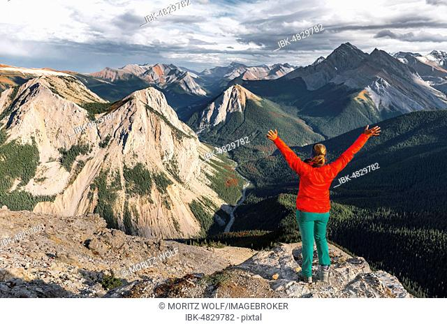 Female hiker with raised arms looking from summit over mountain landscape, summit with orange Sulphur deposits, panoramic view, Sulphur Skyline Trail