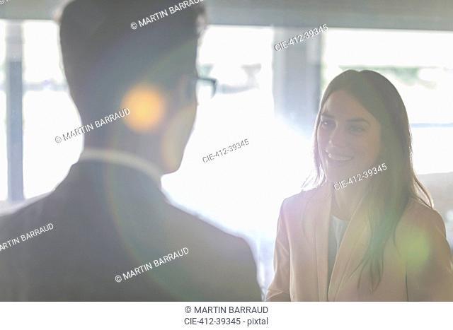 Smiling businesswoman talking to businessman