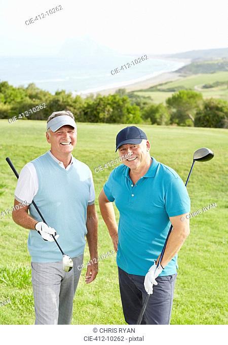 Senior men smiling on golf course overlooking ocean
