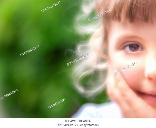 Half face portrait of a cute little Caucasian girl