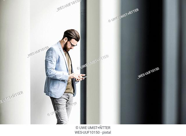 Young businessman standing in office, using smart phone
