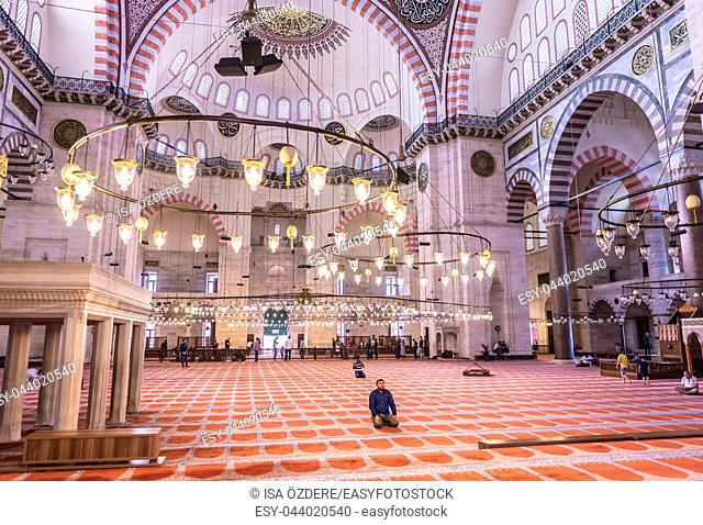 Unidentified Turkish Muslim men praying in Suleymaniye mosque,decorated with Islamic elements and designed by Ottoman architect Sinan. Istanbul,Turkey