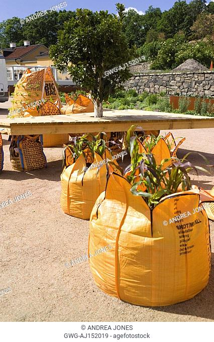 'SHIPPING NEWS'. INSTALLATION BY TOPHER DELANEY USA. LARGE ORANGE BUILDERS BAGS USED TO GROW CORN