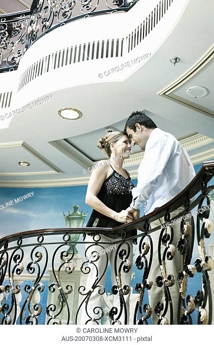 Mid adult couple romancing at a balcony of a ship