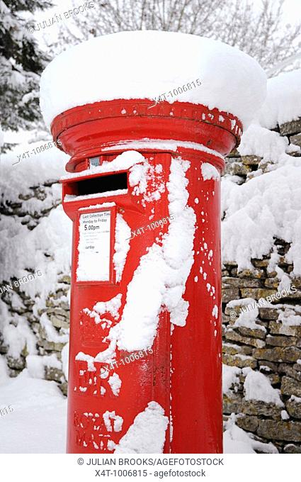 A red pillar box in the snow in the cotswolds