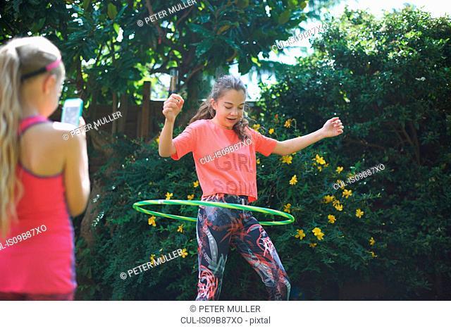 Girl photographing teenage sister hoola hooping in garden