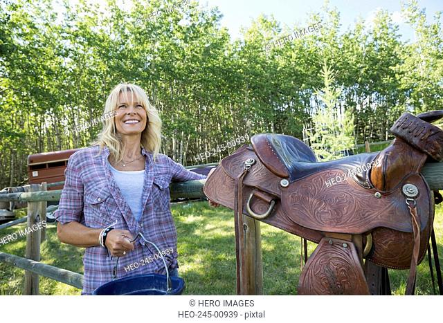 Smiling woman with saddle at pasture fence