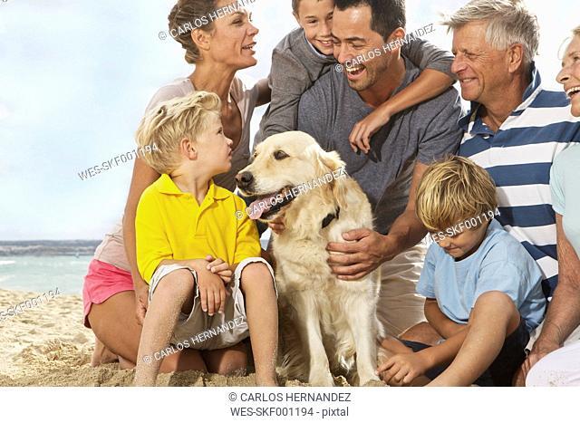Spain, Family sitting on beach at Palma de Mallorca, smiling