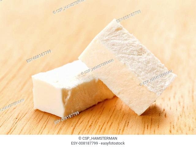 Feta cheese cubes with on wooden chopping board