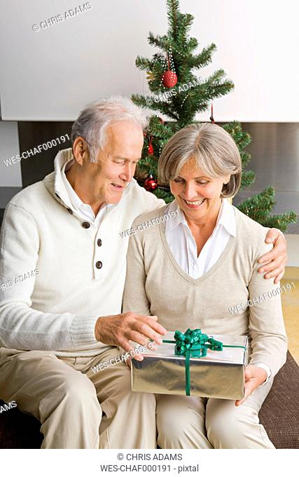 Senior couple exchanging Christmas presents at home