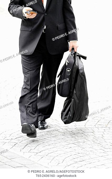 Executive in a suit and briefcase at the mobile while walking, reaching courts Lugo in the Plaza de Aviles