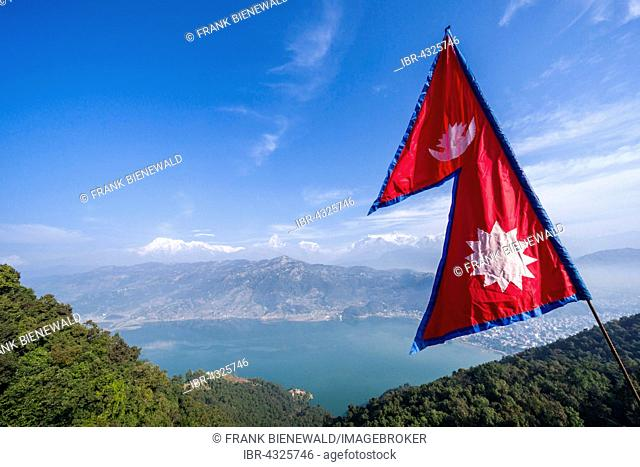 Nepali national flag waving high above the Phewa Lake and Pokhara, Annapurna mountains in the distance, Thumki, Kaski, Nepal