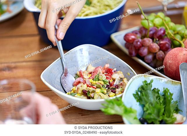people eating salad at table with food