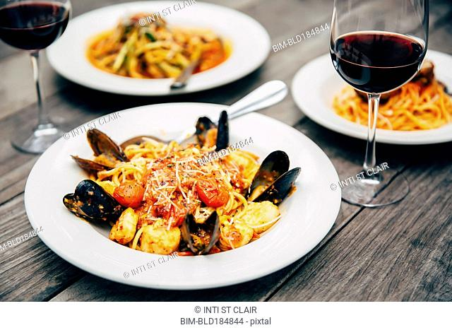 Plates of seafood and pasta with wine glasses