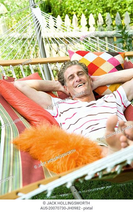 High angle view of a mature man lying in a hammock and smiling