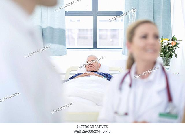 Senior man sleeping in a hospital bed while doctors discussing in the foreground