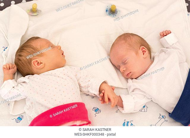 Newborn twins sleeping hand in hand