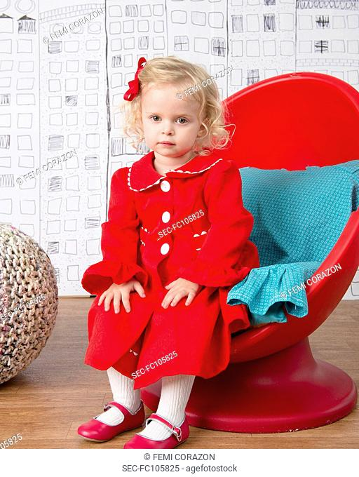 Little girl (2-3) wearing red coat sitting in egg chair