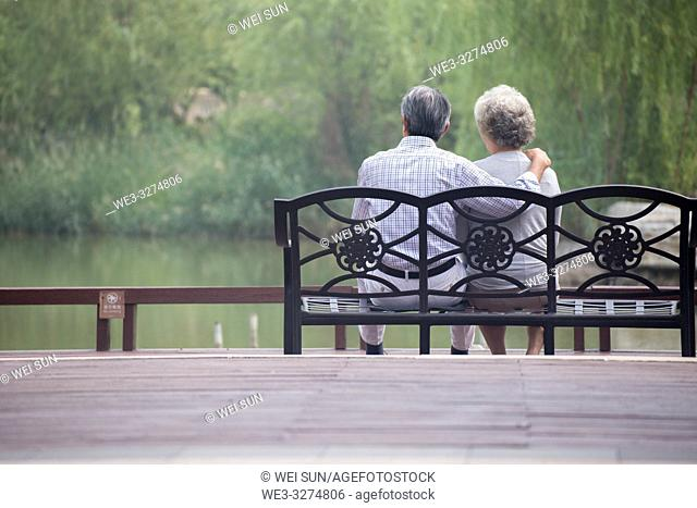Elderly couple outdoors, sitting on bench
