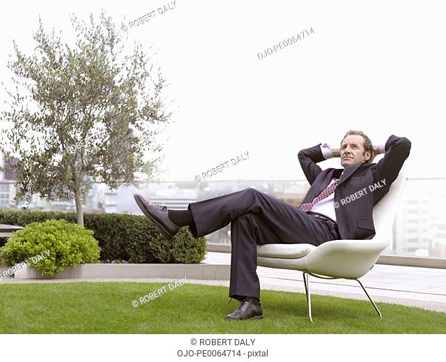 Businessman relaxing in chair outdoors