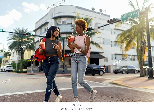 USA, Florida, Miami Beach, two happy female friends having a soft drink crossing the street