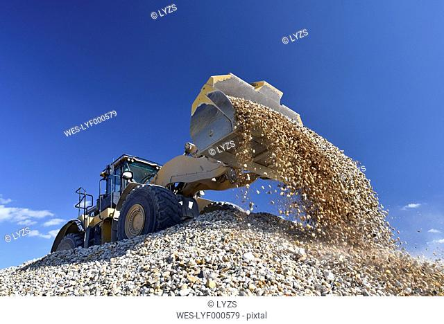 Wheel loader loading stones in gravel pit