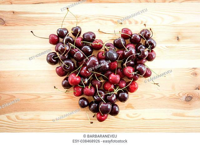 Fresh cherries in heart shape on wooden background