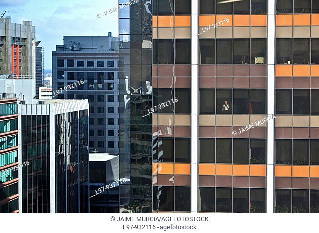 Man on phone standing at office building window