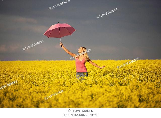 A young woman standing in a rape seed field holding a pink umbrella, close up