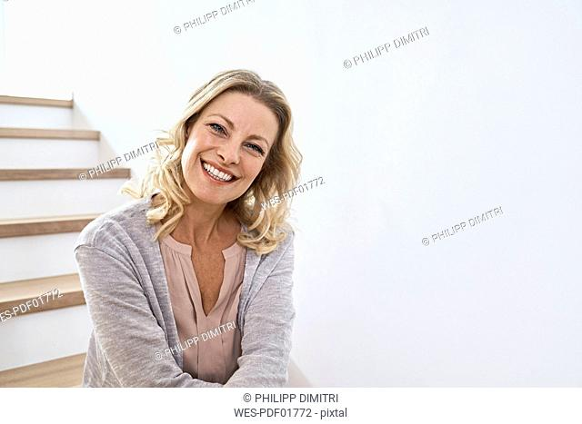 Portrait of smiling woman sitting on stairs at home