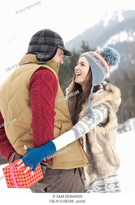 Woman reaching for Christmas gift behind man's back in snowy field