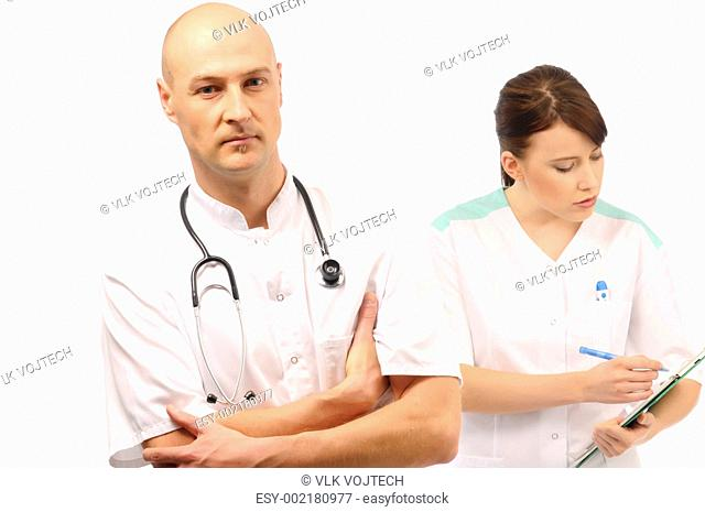 Medical nurse writing notes, doctor next to her