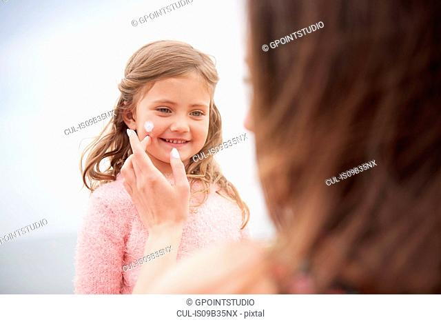 Mother applying sun cream on daughter's cheek
