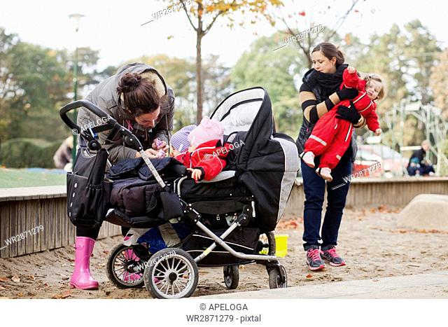 Women with daughters standing in playground at park