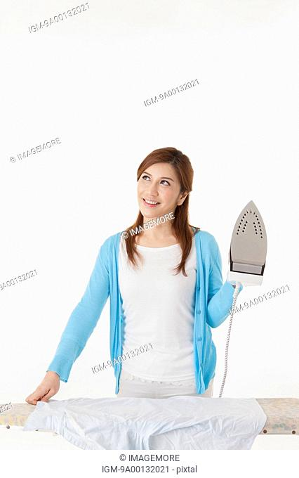 Mature woman holding iron and looking up with smile