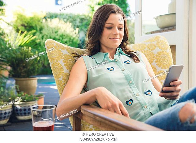 Woman in armchair texting on smartphone