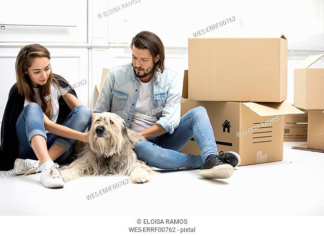 Couple with dog and cardboard boxes sitting on the floor in new home