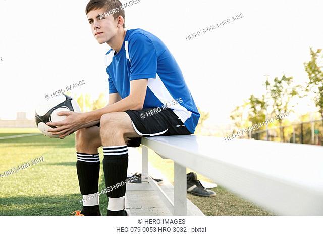 Soccer player holding soccer ball on bench