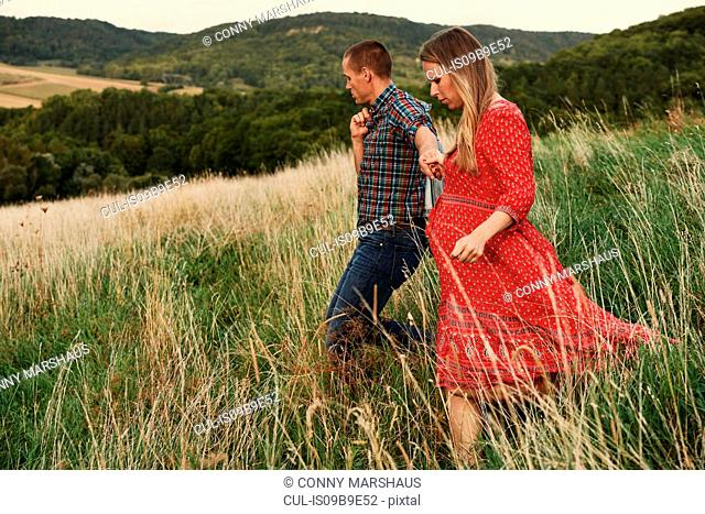 Pregnant mid adult couple holding hands while strolling down hillside