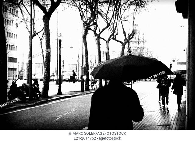 Man with umbrella in a street. Barcelona, Catalonia, Spain