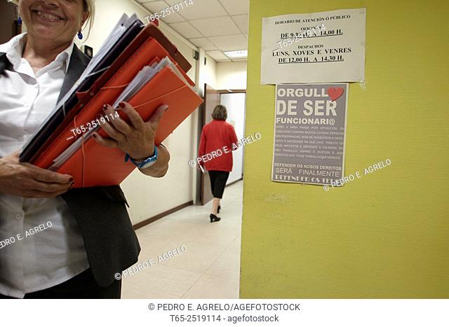 An official with folders in a hallway of an administrative building of the municipality of Lugo