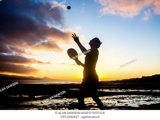 Woman playing beach Tennis at sunset on El Confital beach in Las Palmas, Gran Canaria, Canary Islands, Spain