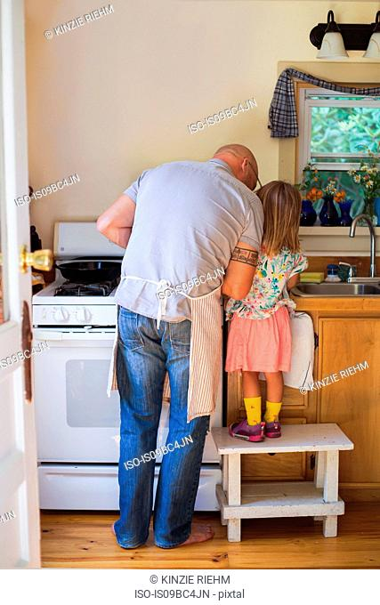 Rear view of girl on stool watching father preparing food in kitchen
