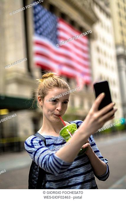 USA, New York City, woman taking selfie in front of New York Stock Exchange