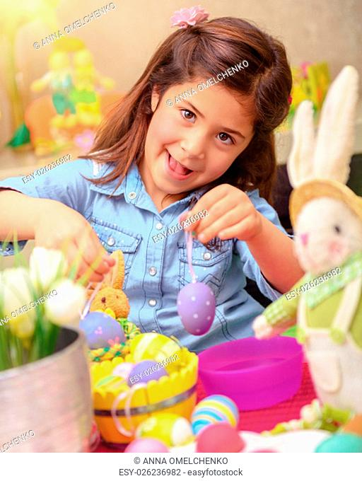 Portrait of cute little girl decorating Easter eggs by different colors, having fun at home with bunny toy, drawing lesson in daycare