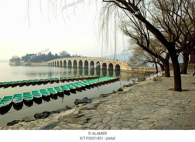 China, Beijing, Summer Palace Yiheyan, boats and Seventeen-Arch Bridge on Kunming lake