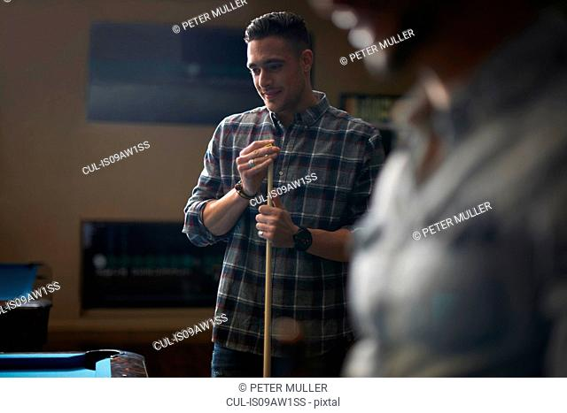 Man with pool cue standing at pool table