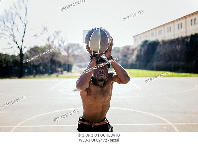 Barechested basketball player on court throwing ball